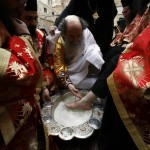 Greek Orthodox Patriarch of Jerusalem Metropolitan Theophilos washes the foot of a priest during the traditional washing of the feet ceremony in Jerusalem's Old City